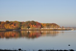 Panoramic view over Greenwich Cove from Tods Point, Greenwich, CT, USA, during late autumn with clear blue sky and trees reflected in water