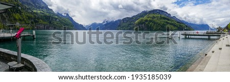 Panoramic view over Lake Lucerne (Switzerland) from the boulevard of Brunnen, with red binoculars and the stone steps of the lake boulevard. Foto stock ©