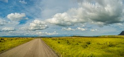 Panoramic view over lonely road through rough and colorful Icelandic landscape, Iceland, summer, blue sky with beautiful clouds