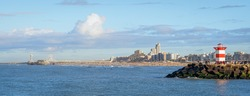 Panoramic view over Scheveningen Pier, beach, and harbor entrance with a lighthouse on a very clear day in January