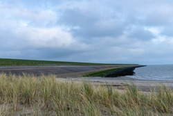 Panoramic view over the eastern shoreline of the island of Texel in the Netherlands with the reinforeced Wadden Sea dike and some dune grass in front and dark clouds