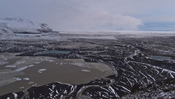 Panoramic view over the glacier lagoon of Skaftafellsjökull with floating icebergs in the south of Iceland in Skaftafell national park with the sparse landscape of Öræfasveit in winter season.