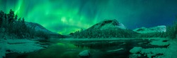 panoramic view over the valley Gjerdalen in northern Norway, with a river and mountain range under northern lights on the night sky.