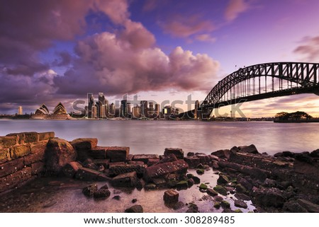 panoramic view to Sydney CBD, Harbour bridge, Harbour and other landmarks from across the Harbour at low tide at sunset