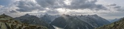 Panoramic view to the Grimsel lake in Swiss Alps with dramatic sun rays breaking through clouds