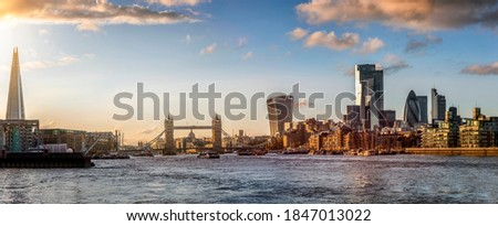 Panoramic view to the modern skyline of London, United Kingdom, with Thames River, Tower Bridge and the City during sunset time