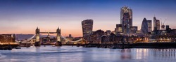 Panoramic view to the skyline of London, UK, just after sunset with the illuminated office buildings in the City and the Tower Bridge