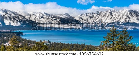 Panoramic view towards Lake Tahoe on a sunny clear day; the snow covered Sierra mountains in the background; evergreen forests in the foreground
