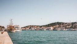 Panoramic view with beautiful harbor and seagulls flying over the village, Croatia. Pleasure boats and yachts with mountain views. Street view