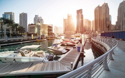 Panoramic view with modern skyscrapers and water pier of Dubai Marina at sunset, United Arab Emirates