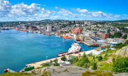 Panoramic views with bight blue summer day sky with puffy clouds over the harbor and city of St. John's NewFoundland, Canada.
