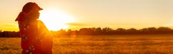 Panoramic web banner African woman in traditional clothes standing, looking, hand to eyes, in field of barley or wheat crops at sunset or sunrise panorama