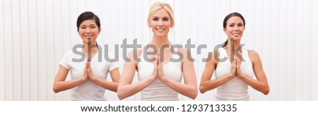 Panoramic web banner interracial group of three beautiful young women hands in prayer practising yoga at a gym or health club