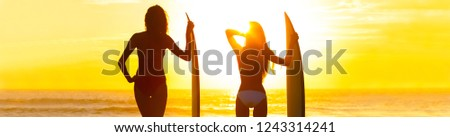 Panoramic web banner rear view silhouettes of beautiful sexy young women surfer girls in bikinis with surfboards on a beach at sunset or sunrise