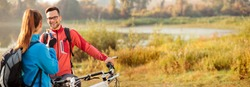Panoramic wide aspect ratio photo of a happy young man and woman resting during an early morning mountain bike ride through countryside, talking and eating energy bars