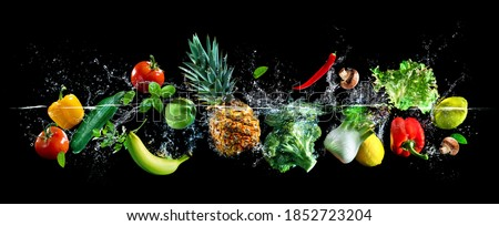 Panoramic wide black background with assortment of fresh vegetables, fruits and water splashes. High resolution collage for skinali
