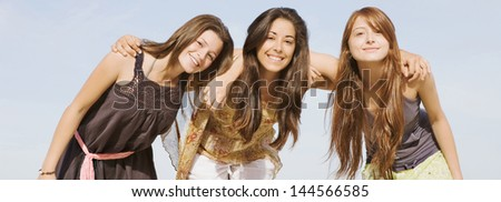 Panoramic wide format portrait of a group of three girls friends smiling to the camera, standing together against a blue sky with their arms around each others shoulders during their summer vacation.