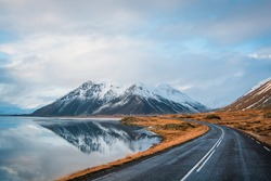 Panoramic winter photo of road leading along coast of lake to volcanic mountains. High rocky peaks covered with snow layer mirroring on water surface. Driver's point of view on Ring road, Iceland.
