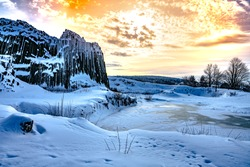 Panska skala - rock formation of pentagonal and hexagonal basalt columns. Looks like giant organ pipes. Covered by snow and ice in winter time. Kamenicky Senov, Czech Republic.