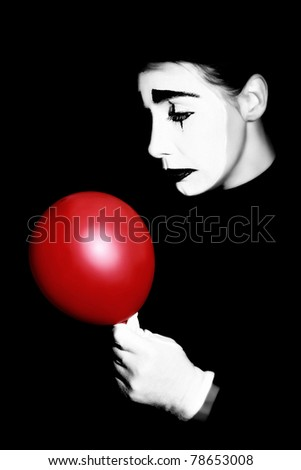 Pantomime. Sad mime performer in dramatic makeup with red balloon isolated on black background.