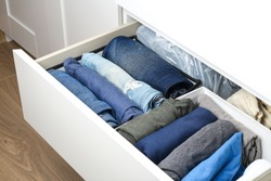 Pants folded according to the method of Marie Kondo. Vertical storage of clothes in a chest of drawers. Storage organization. Order and cleanliness. Quarantine, self-isolation, housework.