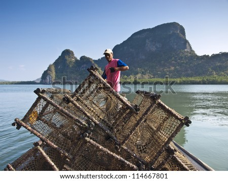 PANYI, THAILAND-FEBRUARY 7: A fisherman uses the net trap for capturing the wild sea fish  on February 7, 2009 in Panyi, Thailand. Panyi island is the unique floating community in south Thailand. - stock photo