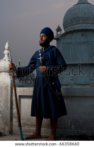 Paonta Sahib, India - May 22, 2009: A young Sikh man holding a sword and spear at the Paonta Sahib Gurudwara, famous for its past warriors