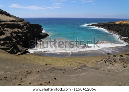 Papakolea (green sand) Beach of the island of Hawai'i surrounded by rocks with beautiful turquoise ocean with foamy waves and blue sky with white clouds #1158412066