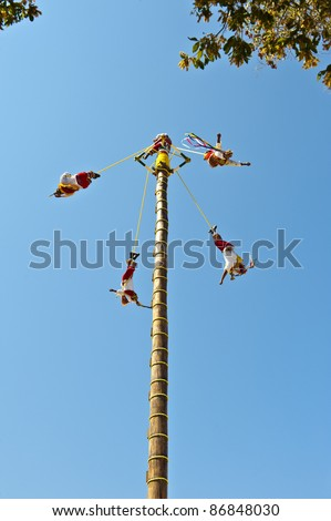 Papantla Flying Men in a clear blue sky of Xcaret Park Cancun, Mexico ancient Mayan Village on July 19, 2011 in Xcaret, Riviera Maya, Mexico