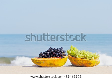Papaya and grape on the tropical beach - stock photo