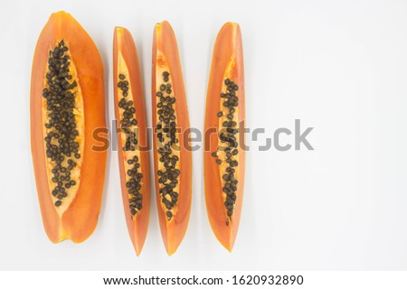 Papaya cut in half in length and on a white surface.Cut many yellow ripe papaya slices in half lengthwise and look at the top corner,Half black papaya seeds, alternating papaya sides Foto d'archivio ©