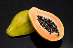 papaya cut in half on a black mirror background