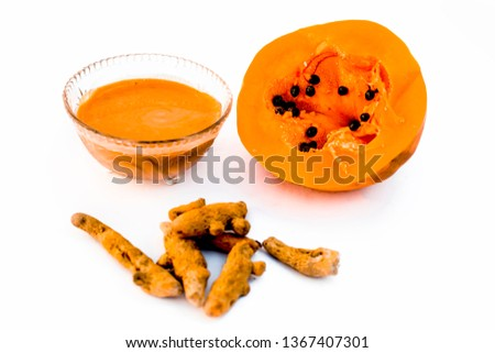 Papaya face mask or ubtan isolated on white i.e. Pieces of ripe papaya and turmeric powder well mixed in a glass bowl and entire ingredients present on the surface.