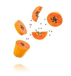 Papaya fruit flying in air, minimal. Tropical exotic orange summer sweet fresh papaya. Colorful levitation concept. Falling fly cut slice orange papaya, fruity creative vivid design