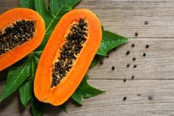 Papaya fruit on wooden background. Slices of sweet papaya on wooden background, Halved papayas