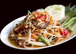 Papaya Salad Thai style (Som tum ) serve with fresh grees vegetable in black background