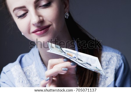 Paper airplane desires. Business woman throwing a paper paper aircraft from the dollars as a symbol of a desire to be successful and to be rich. (Persistence, aspiration, wealth concept)  #705071137