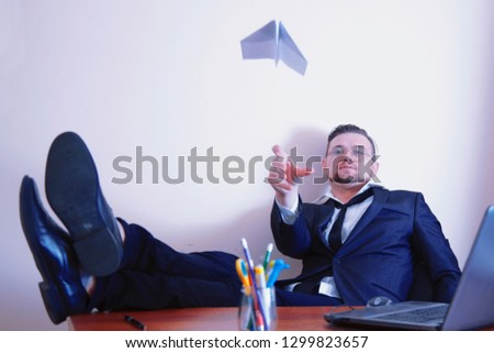 Paper airplane desires. Businessman throwing a paper aircraft as a symbol of a desire to be rich and successful. Purposefulness, persistence, aspiration, wealth concept. #1299823657