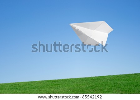 Paper airplane flying over the lawn against the blue sky