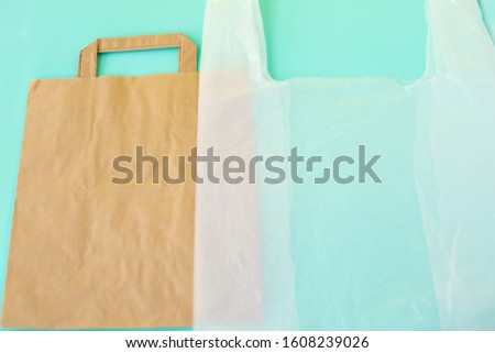 Paper and plastic bag for shopping on blue background. An example of packaging that is healthy and environmentally friendly and then properly recycled and disposed of or damages and pollutes nature