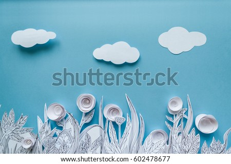 Paper art and origami concept of Flower meadow. White paper flower on blue background. Painted leaves. Copy space