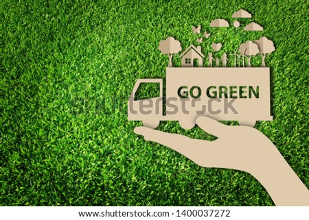 Stock Photo Paper art style of eco on green grass background. Go green. Save the earth.