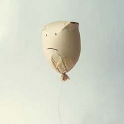 Paper bag balloon with sad face emoji on white background. Creative minimal concept.