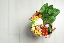 Paper bag full of fresh vegetables on light background, top view. Space for text