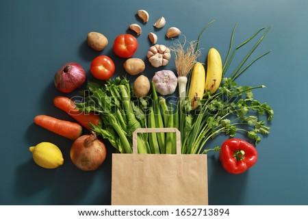 Paper bag of different tropical fresh fruits and vegetables. Healthy eating and grocery shopping concept. Top view. Flat lay Photo stock ©