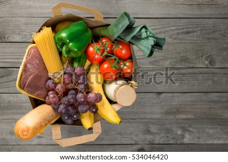Paper bag of groceries on wooden table with copy space, top view