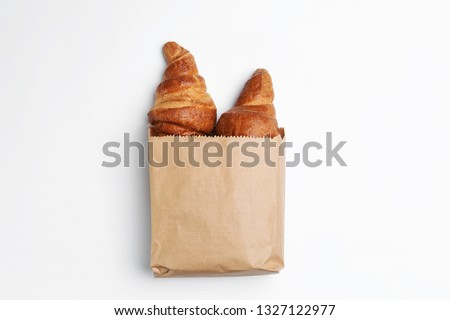 Paper bag with croissants on white background, top view. Space for design
