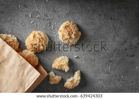 Paper bag with delicious coconut macaroons on table