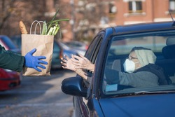 paper bag with groceries handed to needy elderly person in vehicle