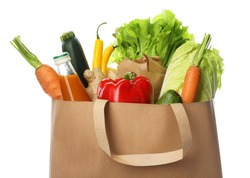 Paper bag with vegetables and bottle of juice on white background, closeup